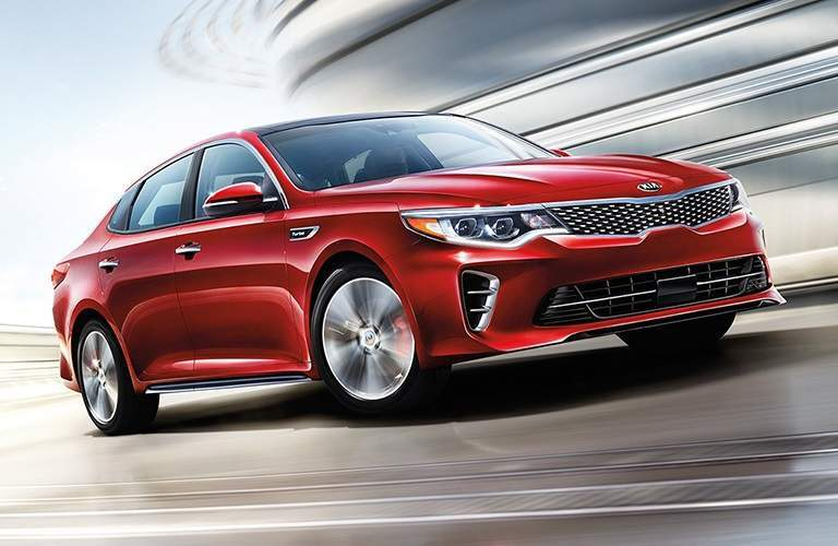 stylized illustration of 2018 kia optima in red driving fast on a track from the ground