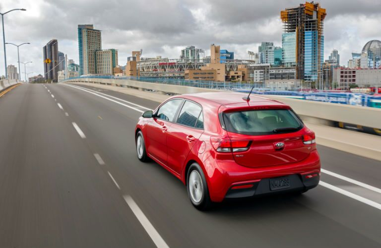 rear driving away of 2018 kia rio 5 door in red
