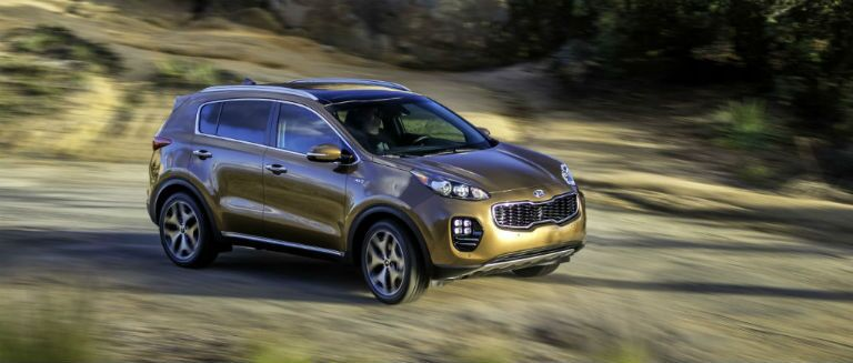 2018 kia sportage in orange driving off-road