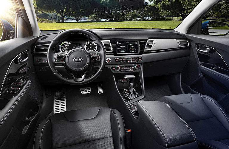 Interior of 2018 kia niro parked on grass somewhere you can see infotainment system and steering wheel