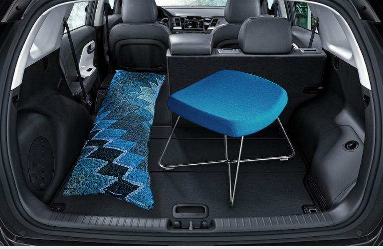 Cargo space in 2018 kia niro shown with rear gate open and chair and pillow inside