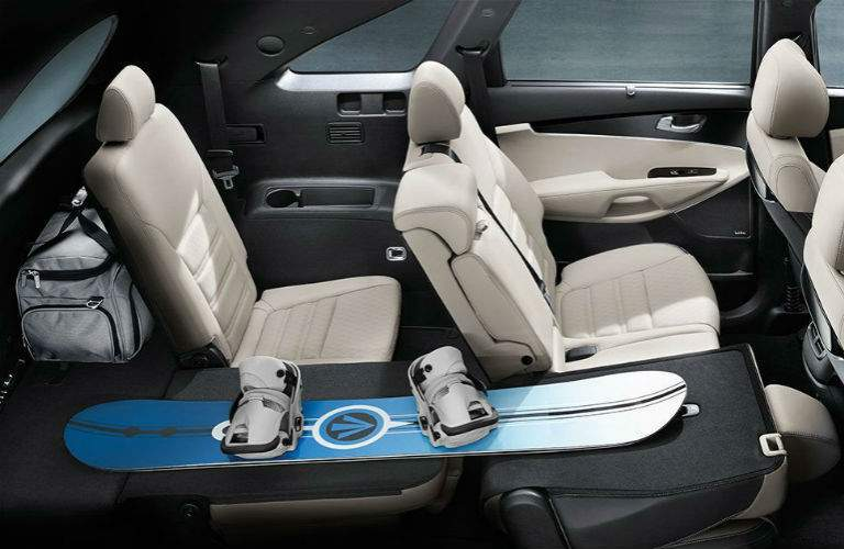 interior of 2018 kia sorento with snowboard stretching from rear area to second row seating