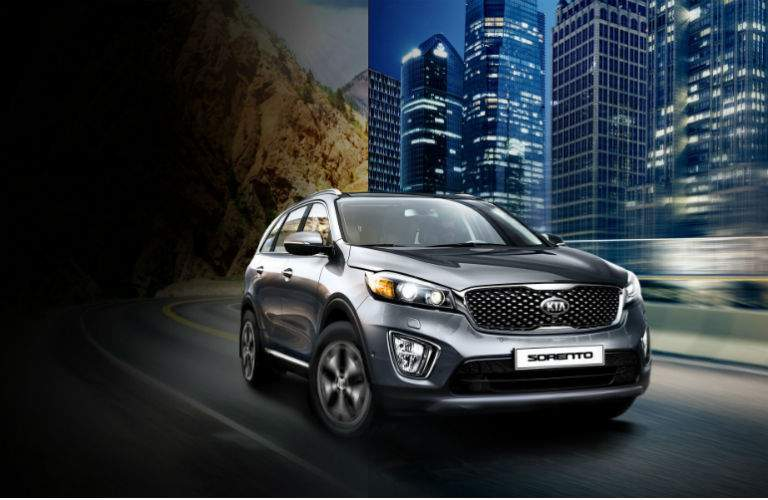 2018 kia sorento in silver driving in a city at night