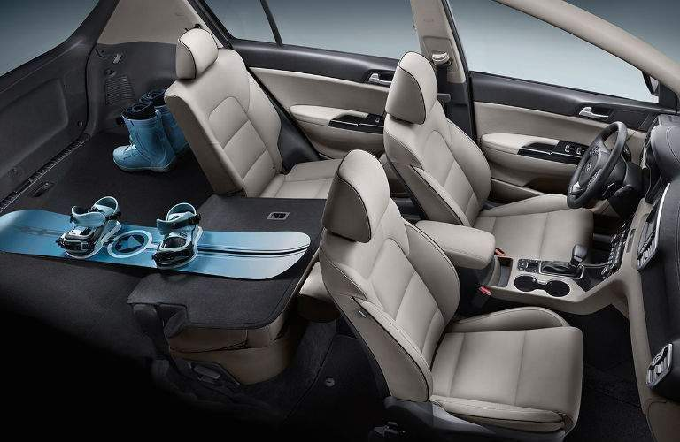 2018 kia sportage sx interior showing bright leather seats and snowboard with seats folded down