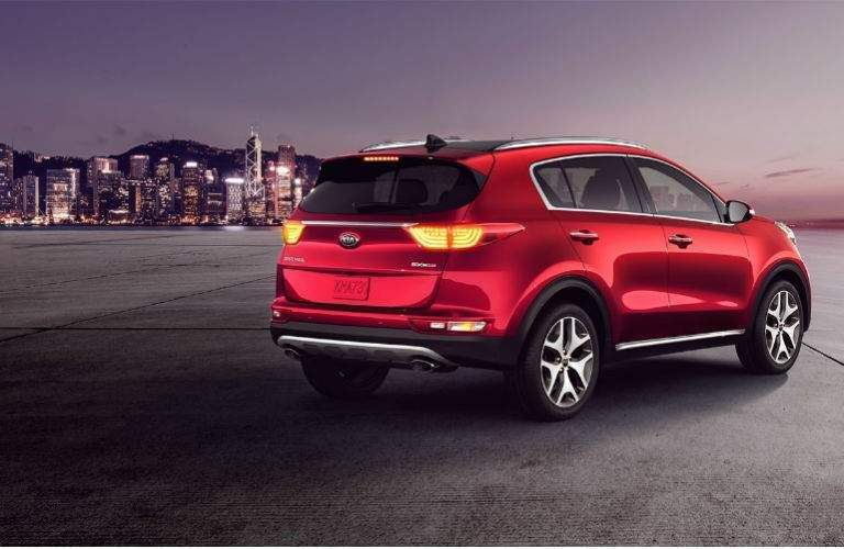 rear three quarter view of 2018 kia sportage in red in front of urban skyline