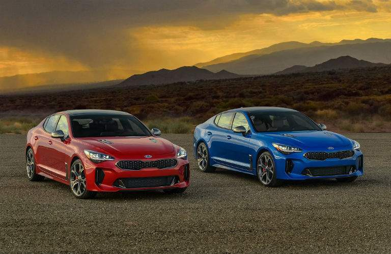 Side by side we see a red kia stinger and a blue kia stinger both models awd gt2 trim