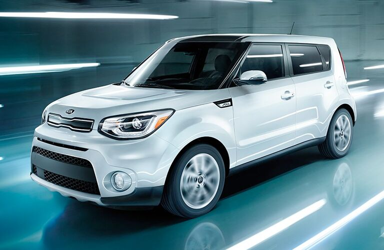 white 2019 kia soul driving in front of stylized lights