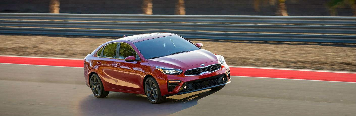 exterior shot of red kia forte driving on track