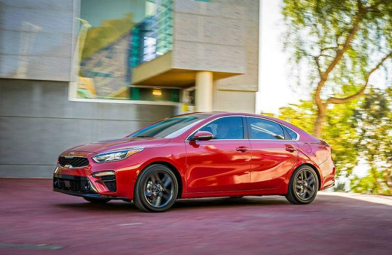profile shot of red 2019 kia forte parked on campus
