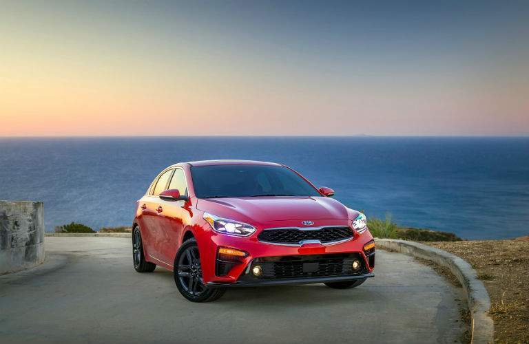 front view of red 2019 kia forte parked in front of sun and ocean