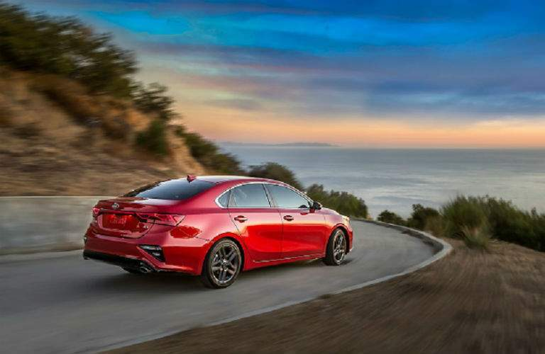 rear shot of 2019 kia forte driving into sunset along coast road