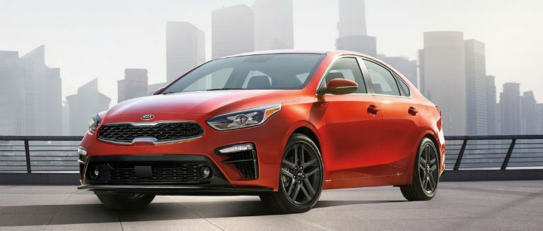 red 2019 kia forte parked on a parking garage roof