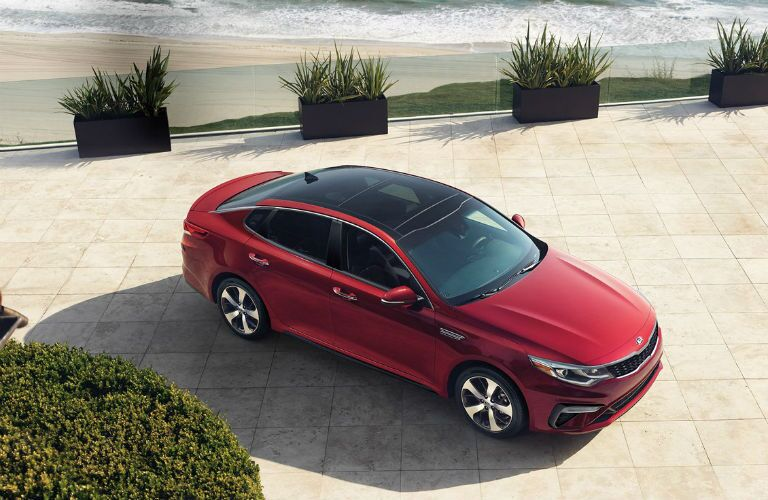red 2019 kia optima on the beach