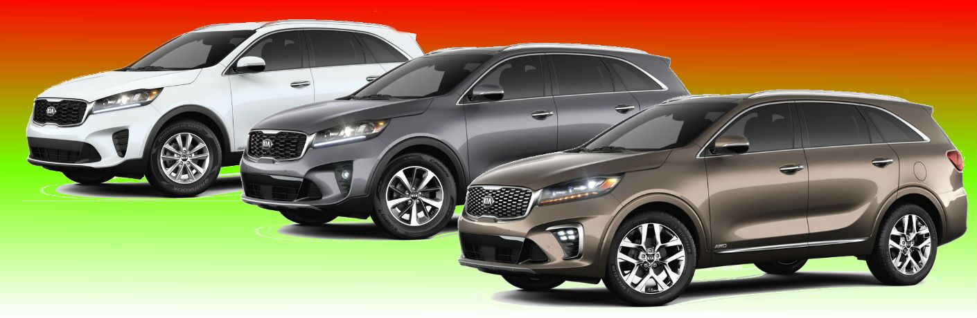 red yellow gradient with three Kia Sorento models posing in front of it