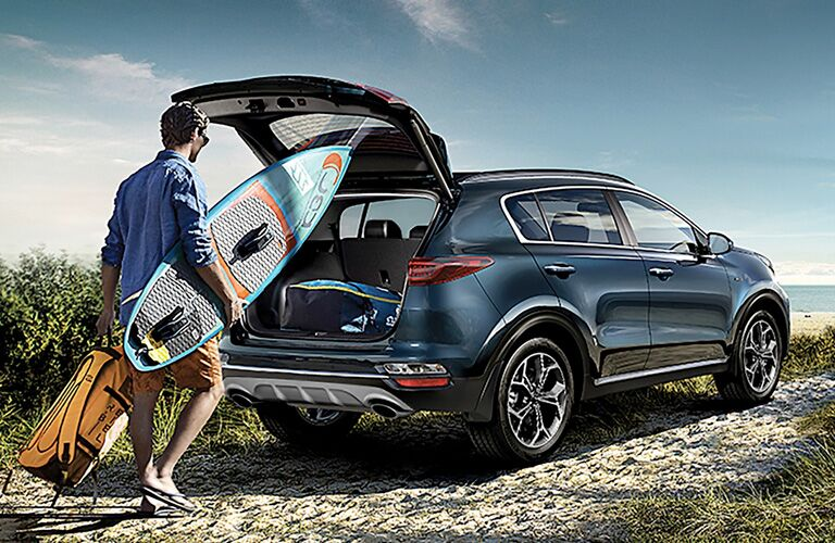 Man with surfboard by rear of 2020 Kia Sportage