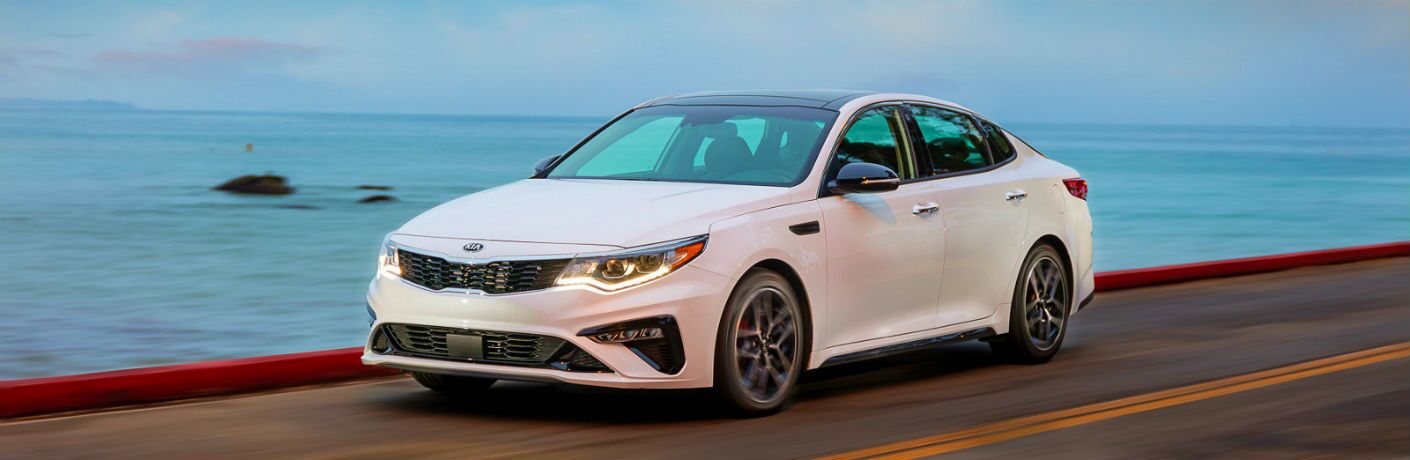 2020 Kia Optima driving along a beach