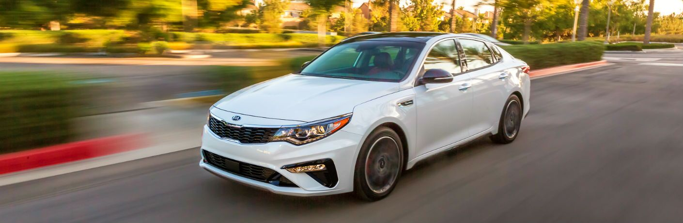 2020 kia optima white driving down road
