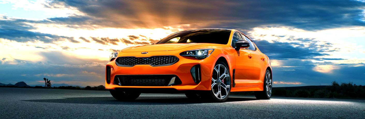 orange 2020 kia stinger gts parked in front of sunrise