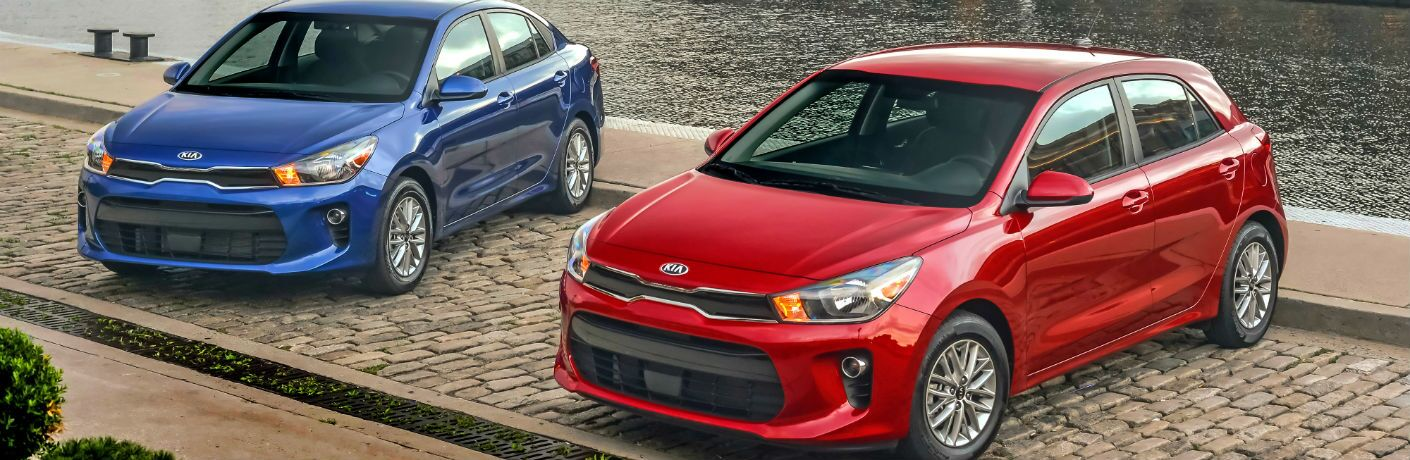 red and blue kia rio by the water