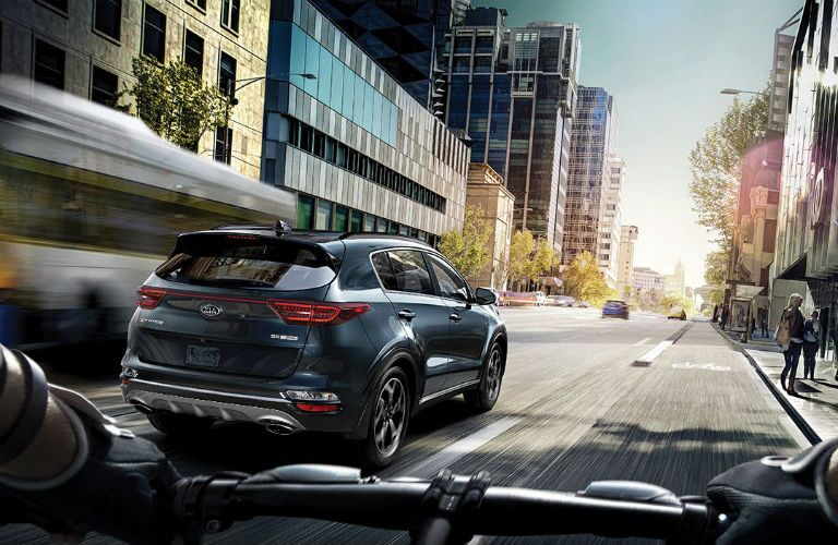 rear three quarter image of 2020 kia sportage driving in the city