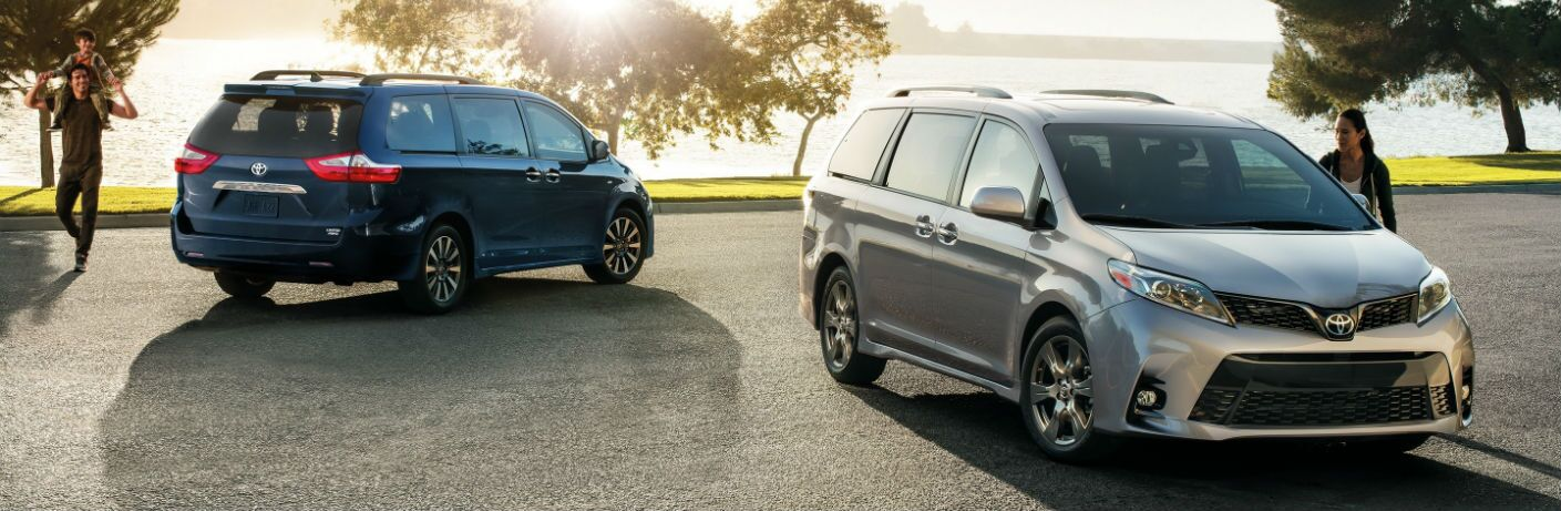 two 2019 Toyota Sienna minivans in a parking lot with a family nearby