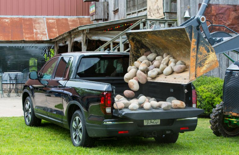 2019 Honda Ridgeline with rocks being loading into truck bed