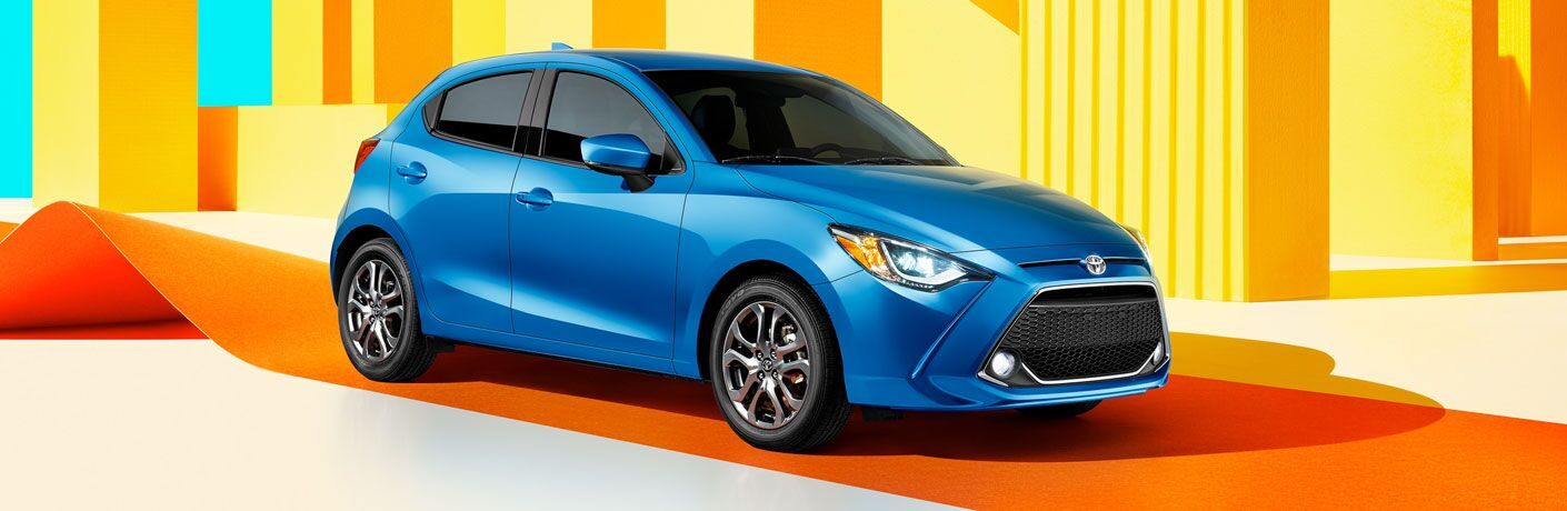 2020 toyota yaris hatchback blue exterior front passenger side parked orange red and yellow graphic background