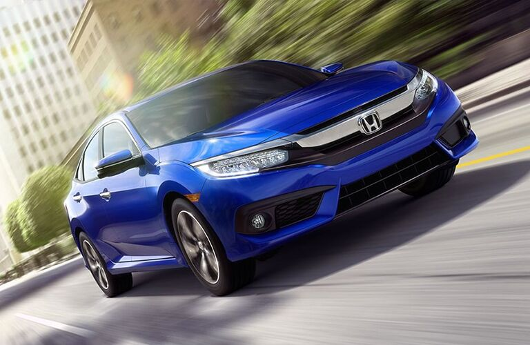 Blue Honda Civic Sedan driving