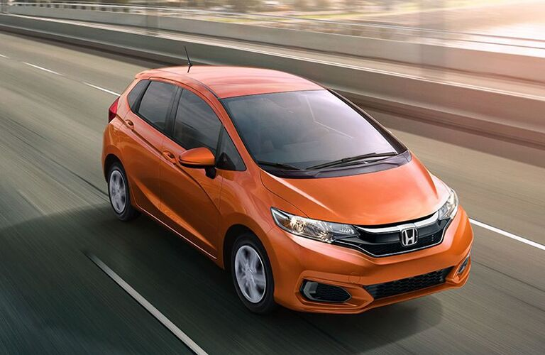 orange Honda Fit driving