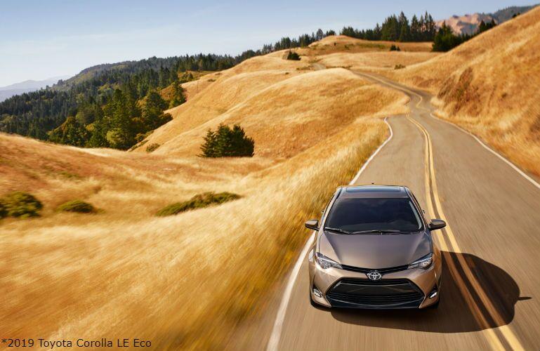 2019 Toyota Corolla LE Eco in Falcon Gray Metallic driving on rural highway