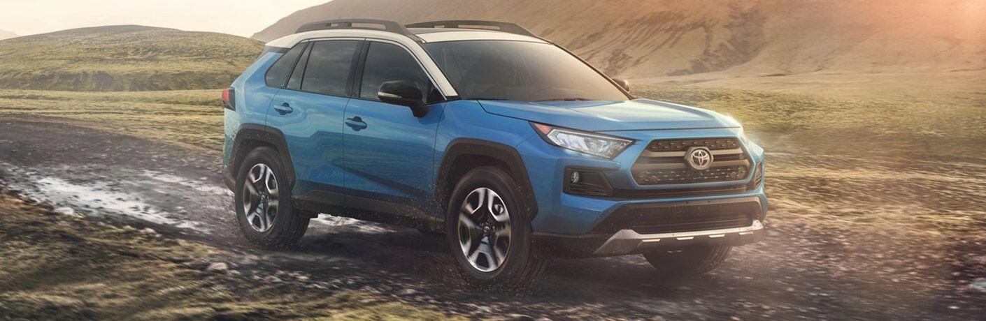 2020 toyota rav4 blue exterior front passenger side driving on muddy road