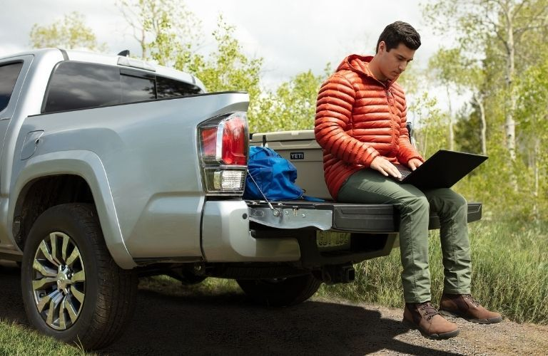 Man sitting on tailgate of 2021 Toyota Tacoma with laptop