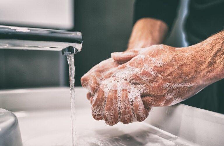 Person washing their hands with soap at a faucet