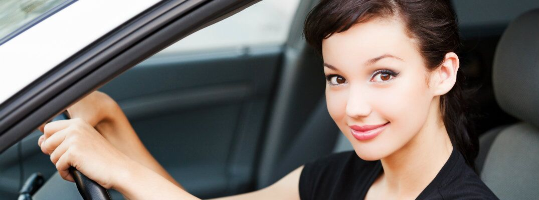 Woman in black shirt behind the wheel of a used vehicle