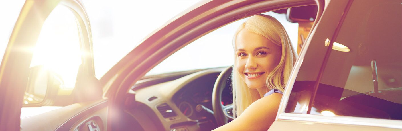 Woman behind the wheel of a used vehicle