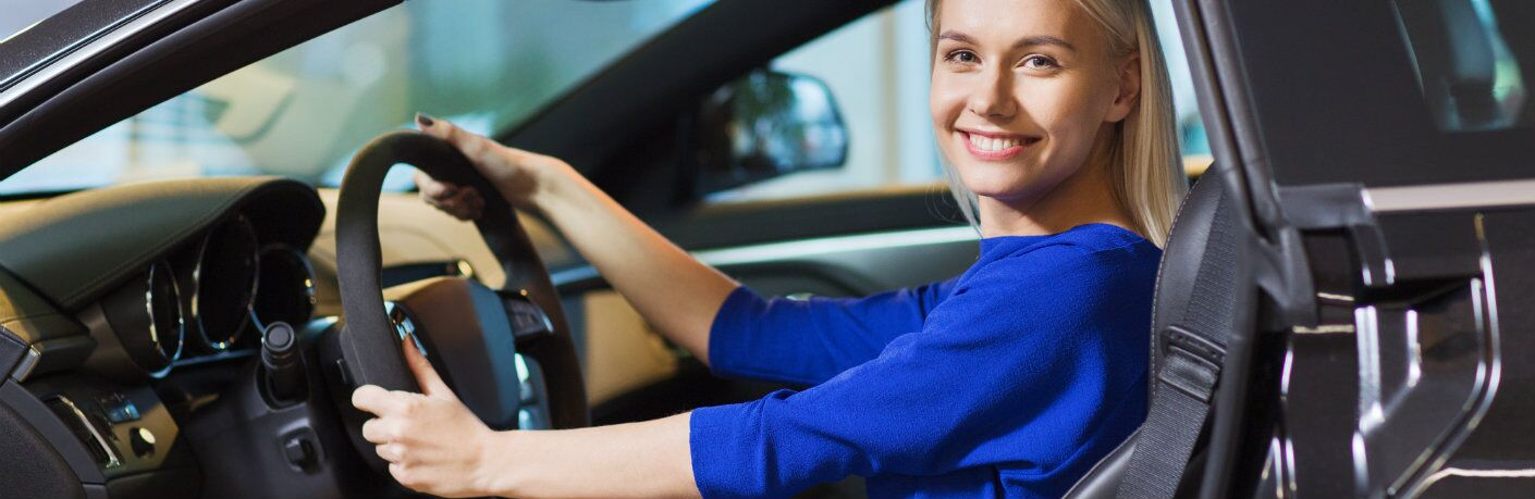 Woman wearing a blue dress while sitting behind the wheel of a car