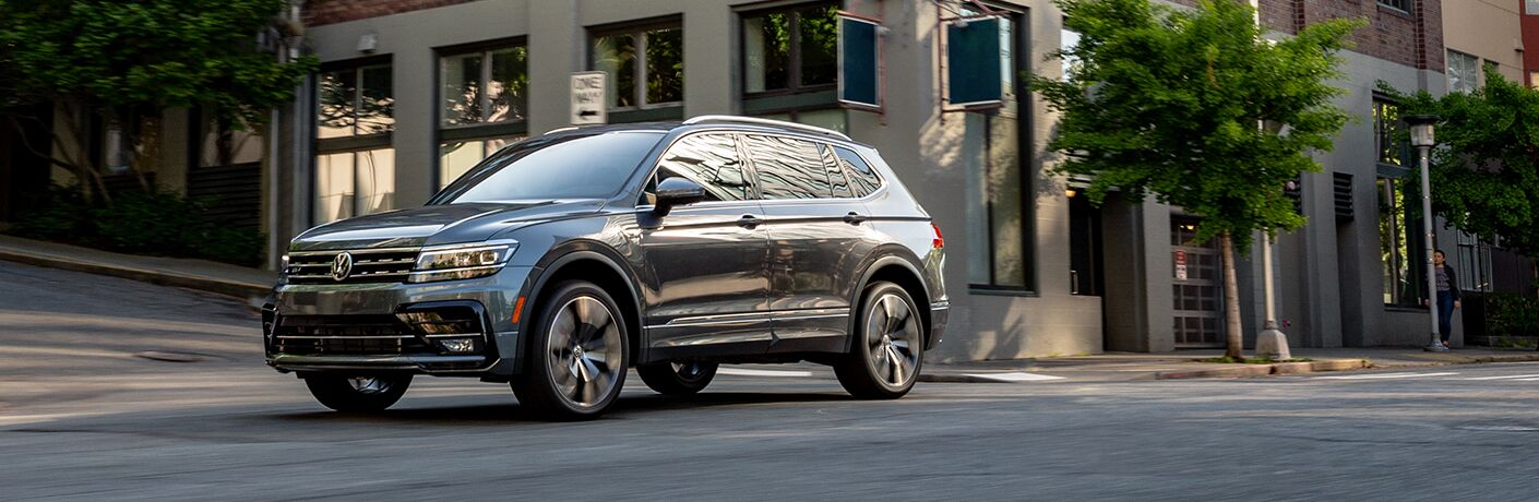 2020 Volkswagen Tiguan black or silver diving down city street with trees and buildings in background