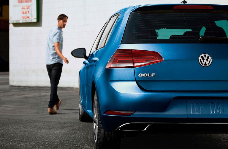 2020 Volkswagen Golf blue shot from behind with man walking toward the front