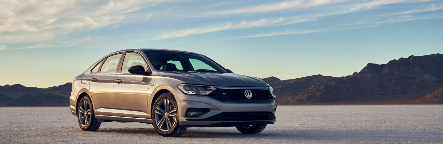 2021 Volkswagen Jetta gray parked on flat gravel in front of mountains