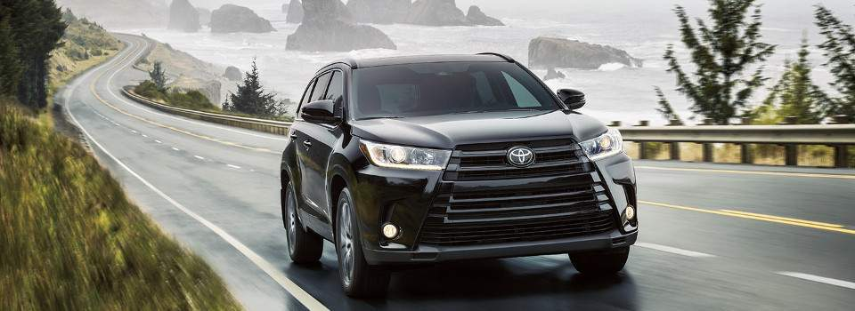 A black 2018 Toyota Highlander driving through the countryside by the sea
