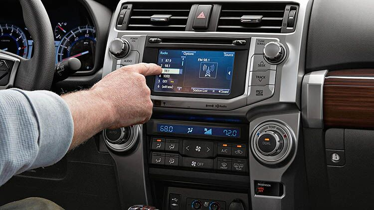 Man's hand touching the tech display panel on a 2019 Toyota 4Runner