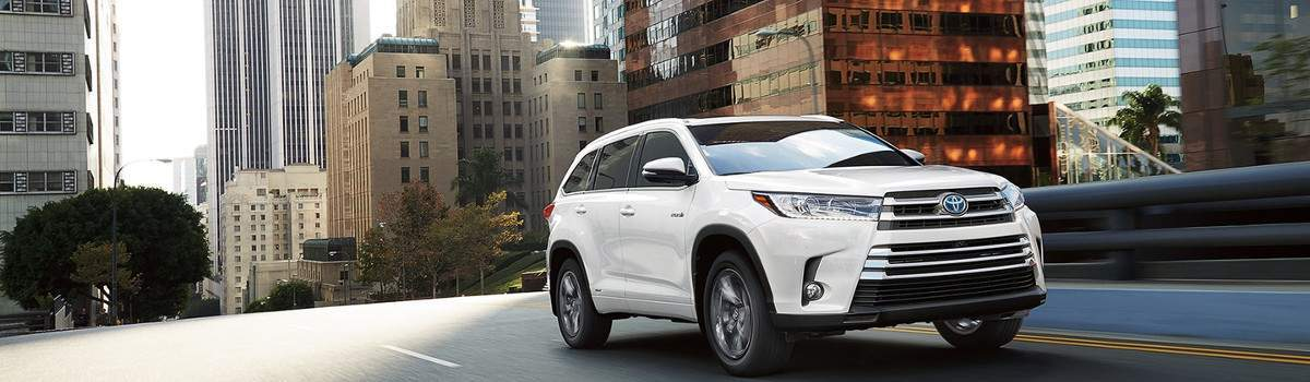 A white 2018 Toyota Highlander driving down the city streets.