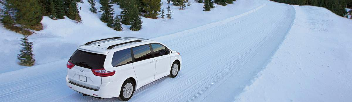 A Toyota Sienna driving down a snowy road
