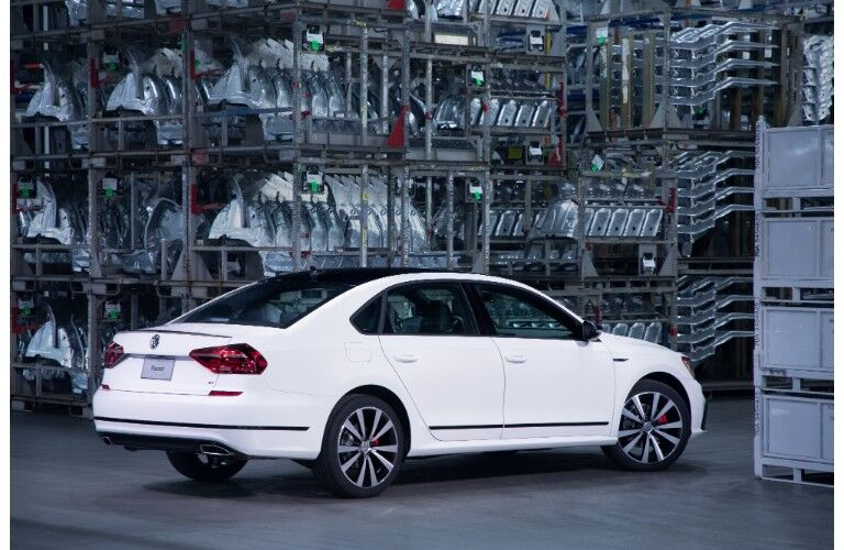 2018 Volkswagen Passat GT exterior side rear shot with white paint job parked in a warehouse of machine parts