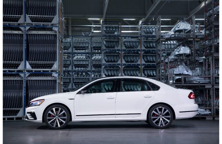 2018 Volkswagen Passat GT exterior side shot with white paint job parked in a warehouse of machine parts