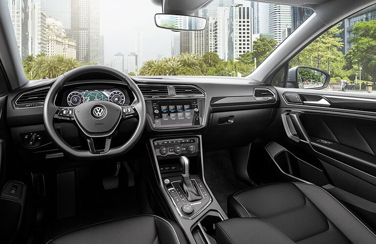 2019 Volkswagen Tiguan interior shot of front seating setup, steering wheel, dashboard display screens, and transmission with a skyscraper city seen through the windshield