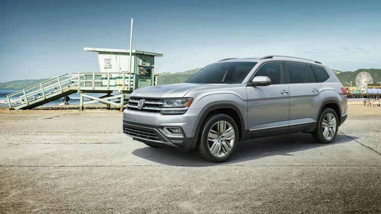 2019 Volkswagen Atlas exterior shot with silver paint color parked near a beach shore lifeguard post