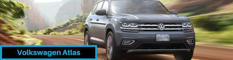 Volkswagen Atlas driving on road between grassy hills
