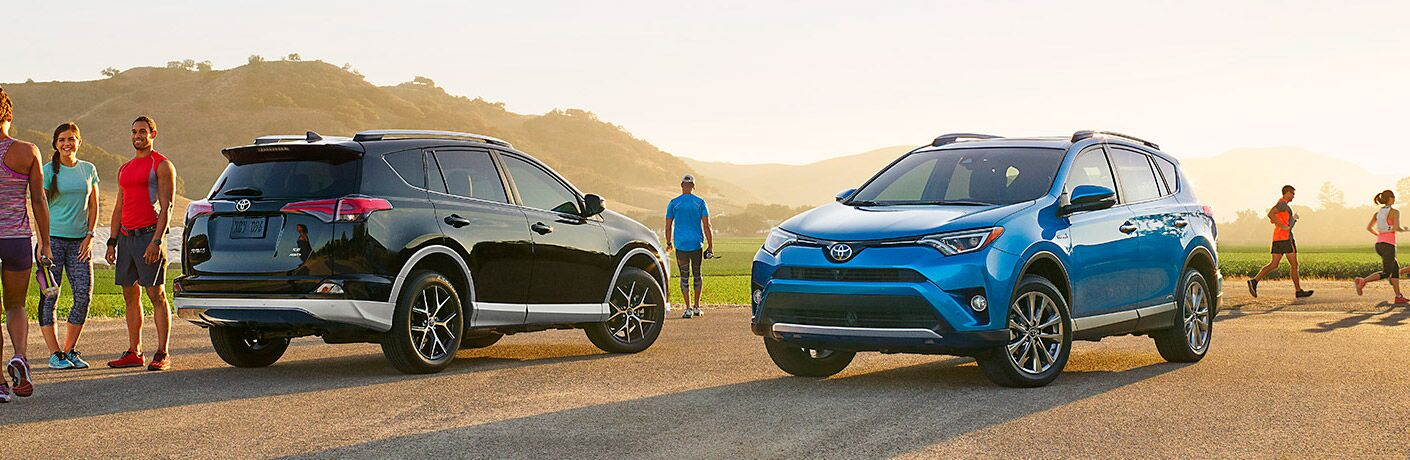 black and blue 2017 Toyota RAV4 models parked with people jogging around them