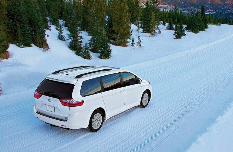 white 2017 Toyota Sienna driving on snowy road